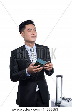 Asian Business Traveler Pulling Suitcase And Holding Passport And Airline Ticket