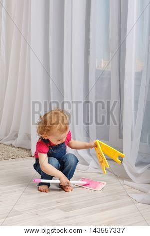 Girl washes the floor mop in the room. Small mother's helper. Household chores.