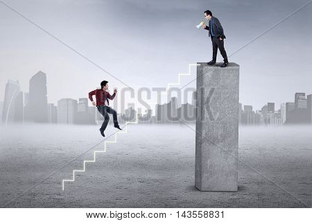 Young entrepreneur standing on the top and call his partner to meet him