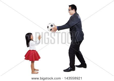 Young businessman wearing formal suit while playing a soccer ball with his daughter in the studio