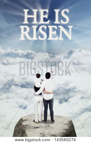 Image of happy Christian family standing at the mountain and look at text He is risen on the sky
