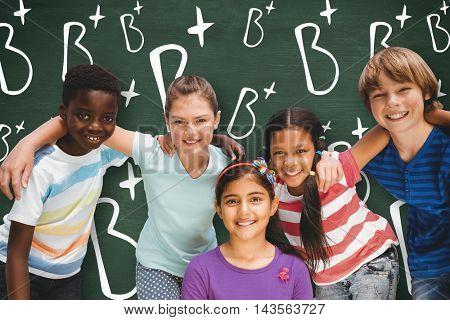 Happy children forming huddle at park against green chalkboard