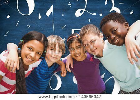 Happy children forming huddle at park against blue chalkboard