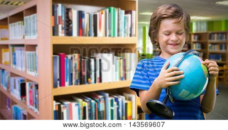 Happy boy holding globe while standing against volumes of books on bookshelf in library Volumes of books on bookshelf in library at the university