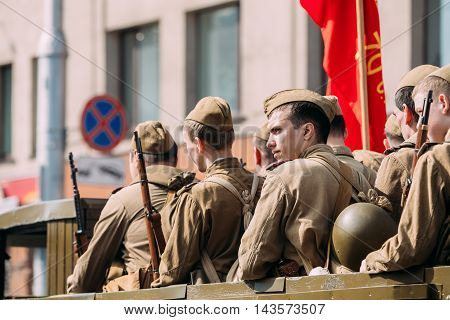 Gomel, Belarus - May 9, 2016: Side View Of Men In Disguise Soviet Soldiers With Guns Sitting In Military Truck ZIS-5V Of WW2 Time With Red Flag. Participants Of Parade Celebrating The Victory Day.