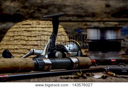 Fishing tackle - fishing rod fishing line hooks and lures on wooden background