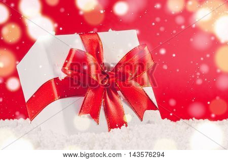 white decorative christmas gift box with ribbon on snow against red festive background