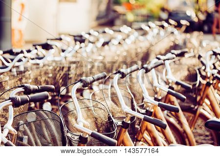 Row Of City Parked Bicycles Bikes For Rent On Sidewalk. Bike Bicycle Parking In European City. Close Up Of Handlebar. Toned Instant Filtered Photo