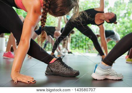 Sports workout background. Back view of women legs in sneakers. Group of sporty people training with fitness instructor on pilates classes. Healthy lifestyle and physical exercises in fitness club.