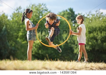 Boy jumps through hula hoop while two girls are holding it