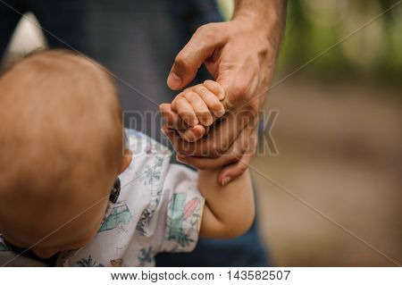 Baby boy learning to walk and making his first steps holding the hands of his father.