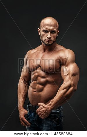 Shirtless muscled fitness man. Cool looking. Tough guy. Bald. Tanned skin. Studio shot on black background.