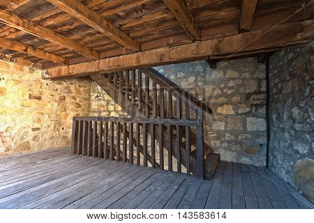Room with stone walls and wooden staircase