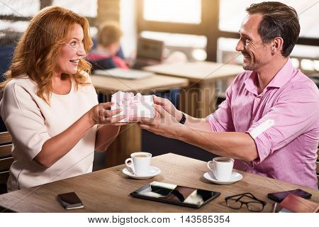 Many happy returns. Smiling man giving a white gift box with rose bow for positive and happy woman