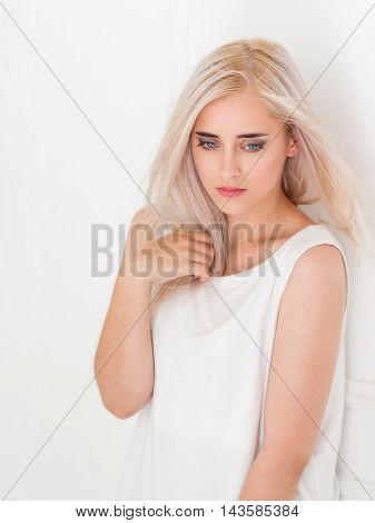 Beautiful blue-eyed blonde with pensive look. Portrait of beautiful thoughtful young woman on white background Melancholy, sadness, depression concept