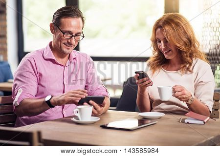 Lunch time. Positive and nice man and woman using their smart phones and drinking coffee while sitting at the table