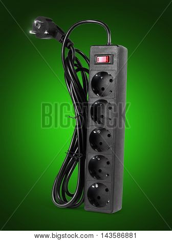 Close up of extension power strip on a green background