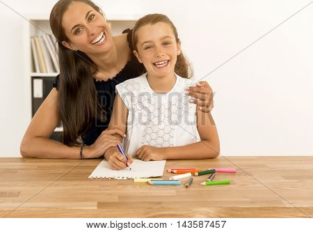 Mother helping her little daughter making drawings