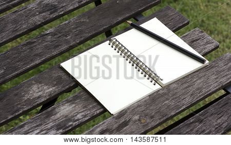 Blank notepad with pencil on office wooden table in park