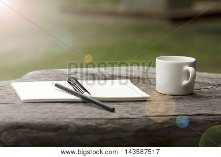 coffee cup with notepad and pencil on wood table in graden