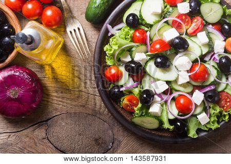 Photo of greek salad on wooden background