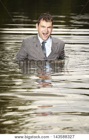 Crazy businessman in suit and tie swimming in river