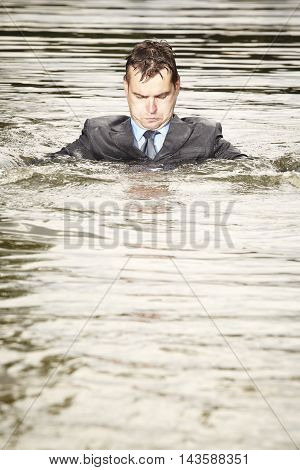 Crazy businessman in suit swimming in summer river