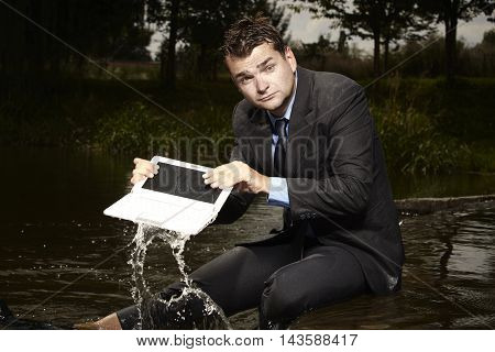 Crazy businessman in suit with notebook in water