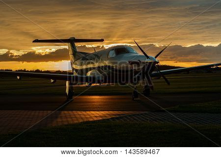 Single-engined business airplane on runway at sunset time.