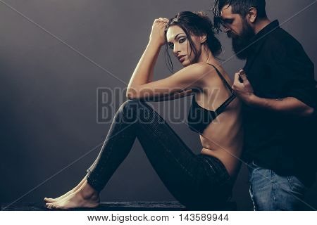 young couple of pretty sexy woman in black jeans and bra has slim body and handsome bearded man with long beard in shirt on grey background copy space