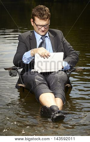 Businessman in suit and tie relaxing after burning out in water