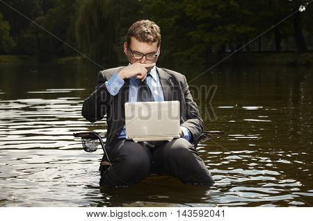 Businessman in suit relaxing in water on folding chair