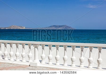 Sea and fence with white balusters and blue sky