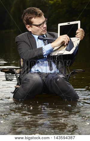 Crazy businessman in suit cleaning wet notebook