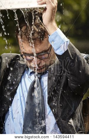 Crazy businessman in suit pouring water from notebook
