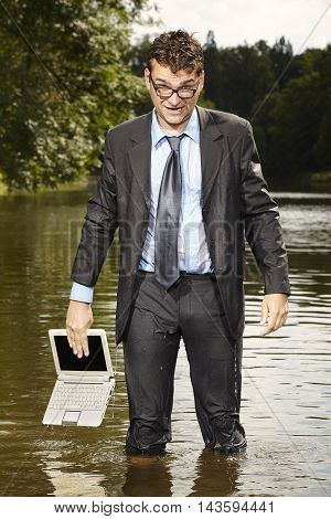 Crazy businessman trying to save notebook from water