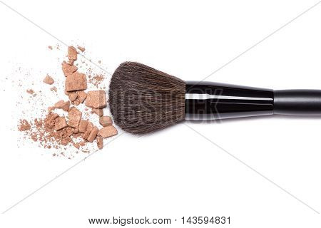 Close-up of crushed bronzing powder with makeup brush on white background. Bronzer to create a tanned look or light contouring on the face