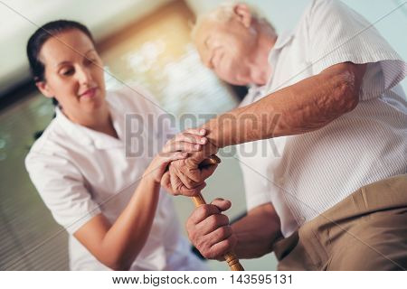 Young woman holding hand of old man with walking stick