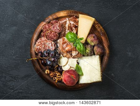 Italian antipasti snack for wine. Prosciutto di Parma, salami, cheese variety, figs, grapes, peach, walnuts and fresh basil on wooden serving tray over dark grunge background. Top view