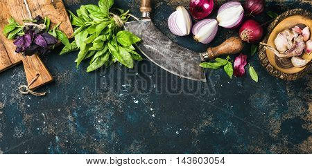 Healthy food cooking background. Fresh green and purple basil leaves, red onions and garlic with herb chopper knife and rustic cutting board over grunge dark blue plywood texture. Top view, copy space