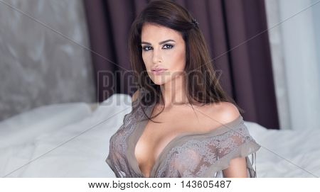 Sensual Girl Sitting On White Bed.
