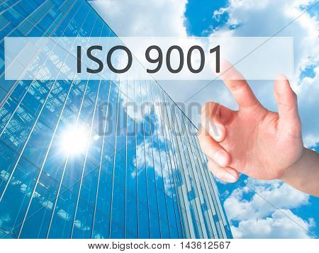 Iso 9001 - Hand Pressing A Button On Blurred Background Concept On Visual Screen.