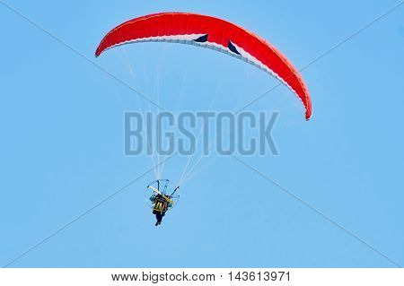 Paraglider with motor floating against a blue sky