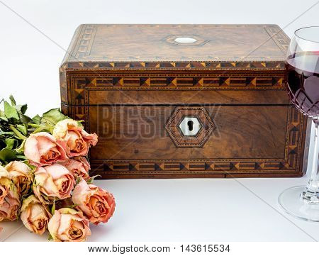 Background with pink dried roses antique walnut jewelry box with mother of pearl inlay and red wine in crystal glass isolated on white background