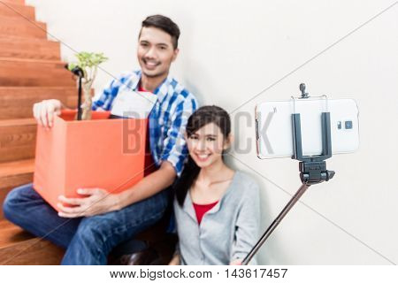 Asian couple, woman and man, taking selfie from their moving day sitting tired on the stairs to their new apartment