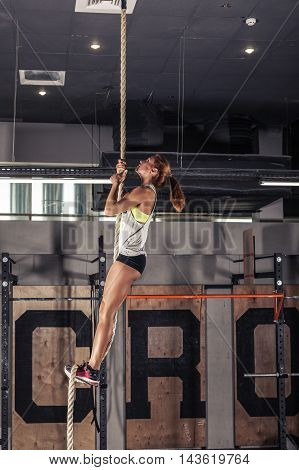 Fitness rope climb cxercise In gym. Girl training in gym