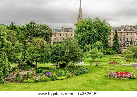 Flower beds, grass and trees in public park of Bath, England on grey overcast day.