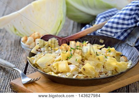 Vegetarian pasta with fried white cabbage and onions, an Austrian specialty called 'Krautfleckerl', served in an iron frying pan