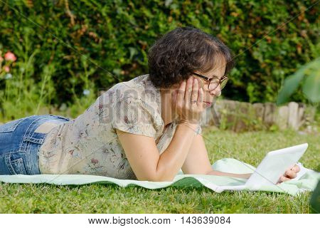 mature woman is resting in the garden with digital tablet