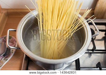 Spaghetti in pan cooking in boiling water.